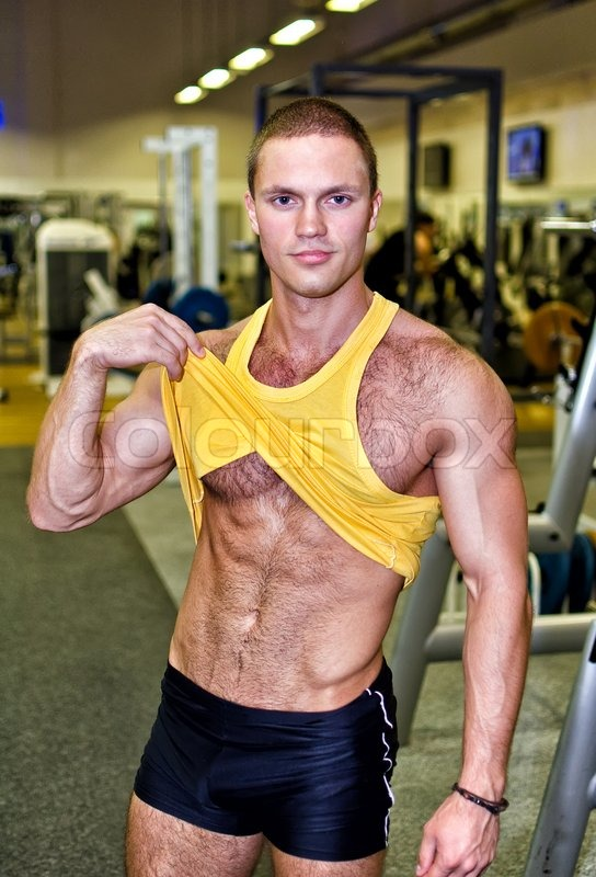 Handsome Bodybuilder Showing His Body In A Gym Stock