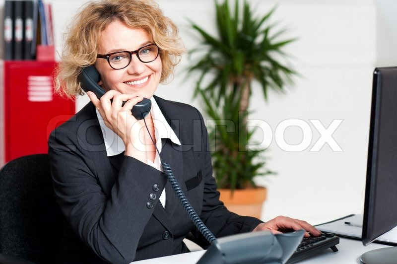 Stock image of 'Front desk lady attending clients call'