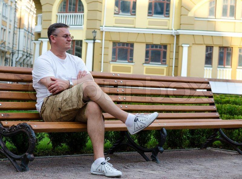 Man Sitting Waiting On An Urban Bench Stock Photo
