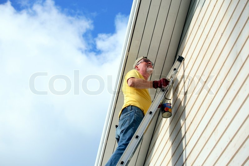 painting a wallSenior man standing high up on a ladder painting a wall  Stock
