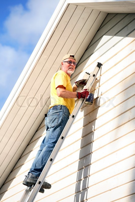 Senior man painting the gable of his     | Stock image