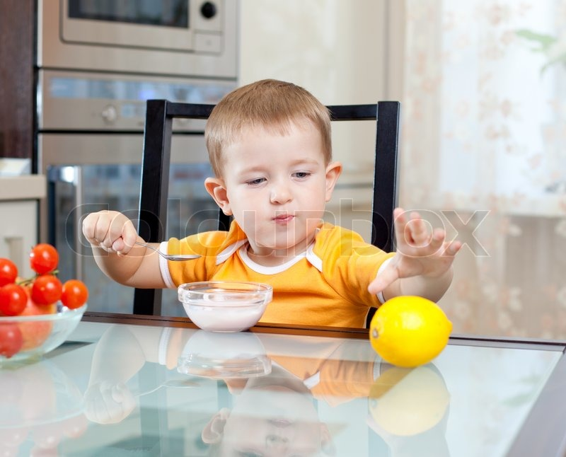 cute little boy eating healthy food at kitchen stock photo colourbox