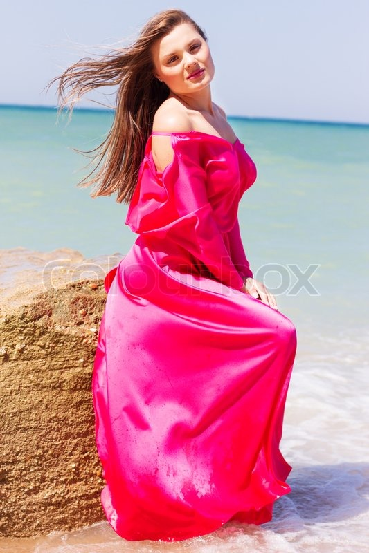 Outdoor portrait of young smiling woman in long red dress in the sea