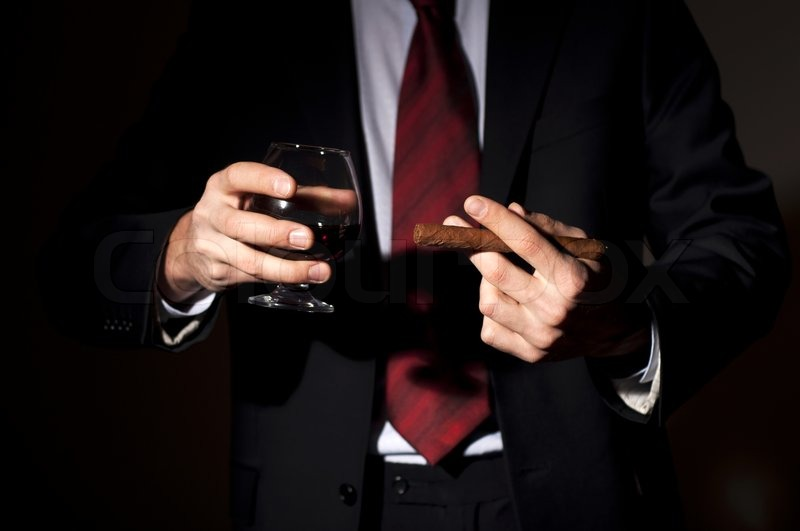 Man In A Business Suit Holds A Cigar And A Glass With