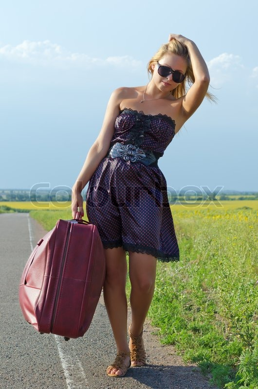 Woman walking with luggage in the country | Stock Photo | Colourbox