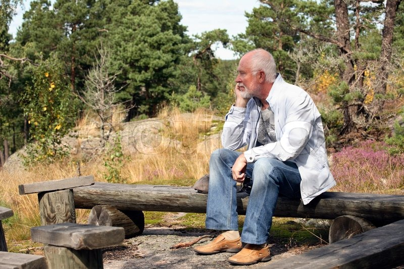 Sad senior man sitting alone on a bench in forest | Stock