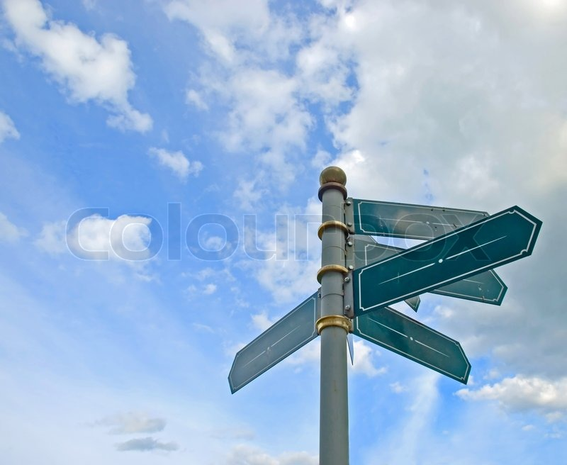 blank old directional road sign post over blue sky stock photo