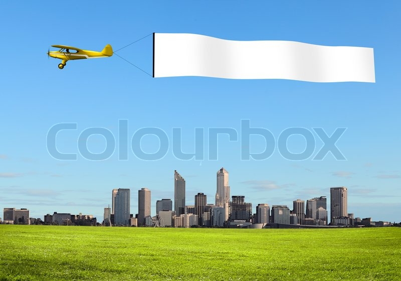 plane in the sky above the city with blank flag stock photo