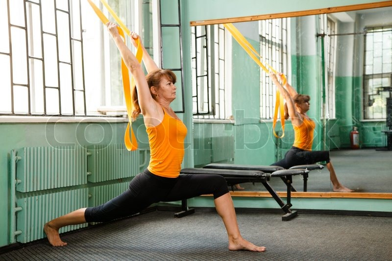 Stock image of 'Mature woman exercising yoga'
