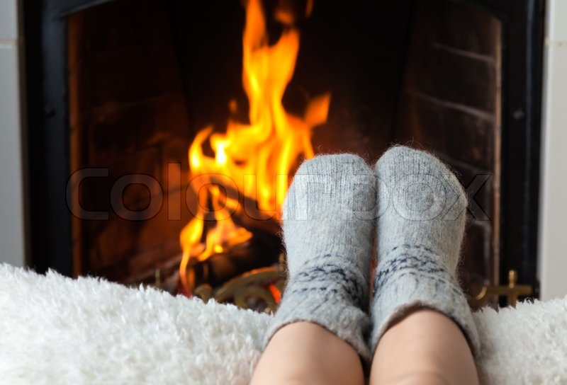 Childrens feet are heated by the fireplace Stock Photo Colourbox