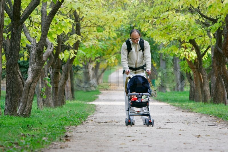 Father And Baby In Stroller Walking In Park Stock Photo