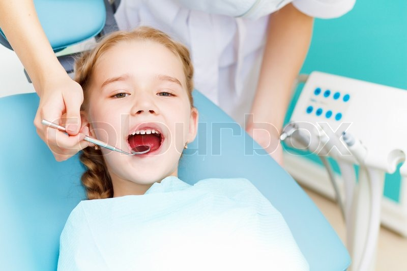 Stock image of 'Little girl sitting in the dentists office'