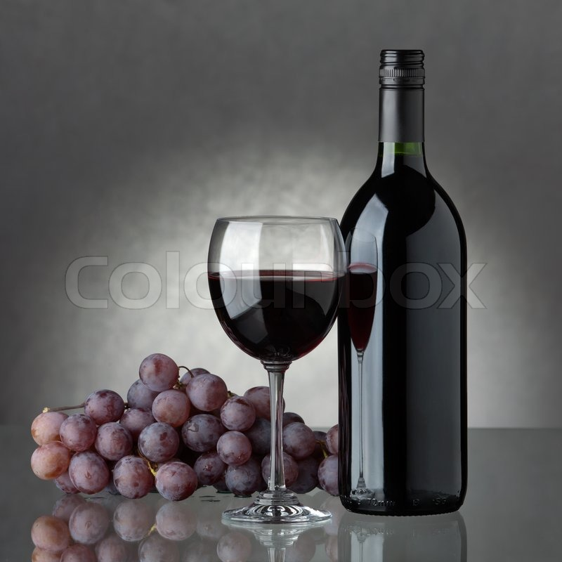 A bottle of red wine glass and grapes stock photo for Red glass wine bottles suppliers