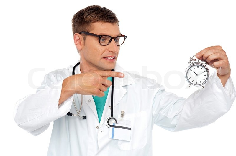 Stock image of 'Shocking young doctor pointing at alarm clock'