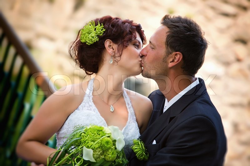 Groom Kissing Bride On Their Wedding Day