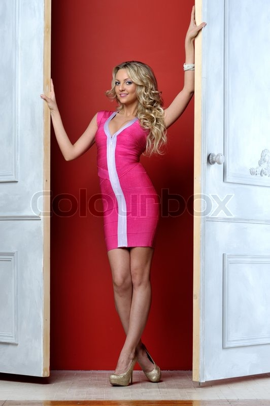Beautiful blonde woman in a pink dress at the opened white door stock photo