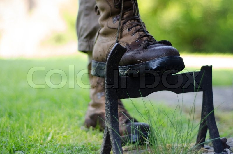A walker cleaning the solesof walking boots on an old cast
