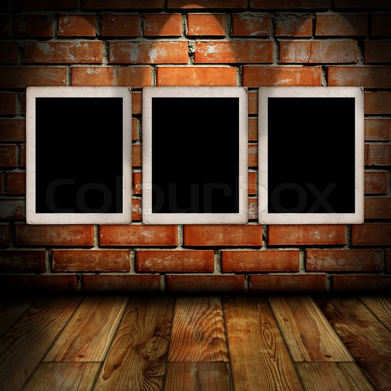 empty frames in a room against a brick wall stock photo