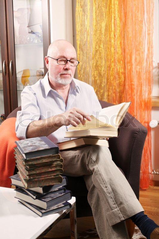 Alter Mann Liest Ein Buch Sitzt In Seinem Sessel Im Wohnzimmer Mit Einem Stapel B 252 Cher Auf Dem