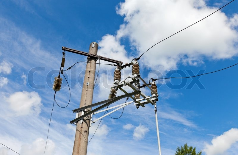 Electric power post with wire against bright blue sky and clouds ...