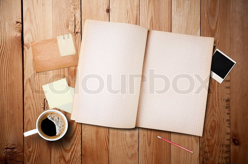 Workspace with coffee cup, instant photos, note paper and notebook on old wooden table, stock photo