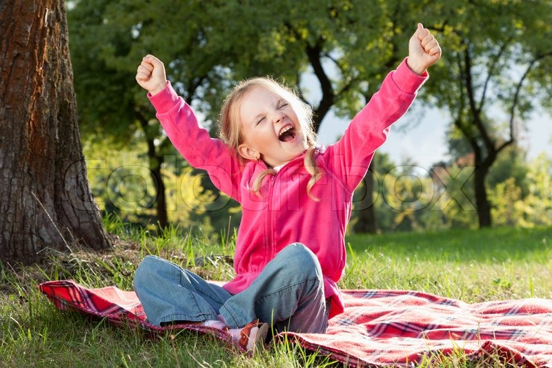 Happy little girl with hands up in summer park | Stock ...