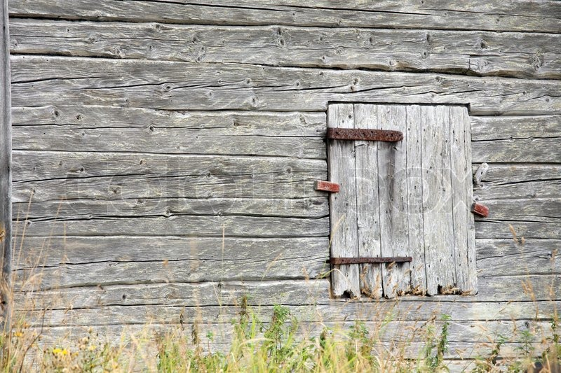 Old Grey Barn Wall Made Of Logs With Closed Door And