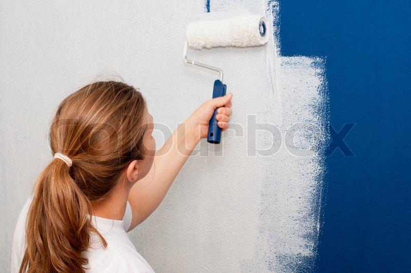 painting a wallWoman painting a wall  Stock Photo  Colourbox
