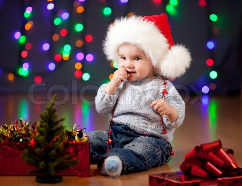 86e6a6b6e14a2 Funny baby in Santa Claus hat on bright ...