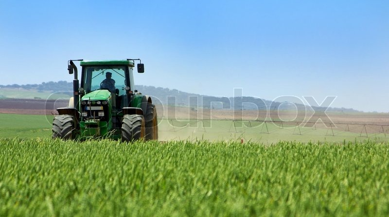 Green tractor working, stock photo