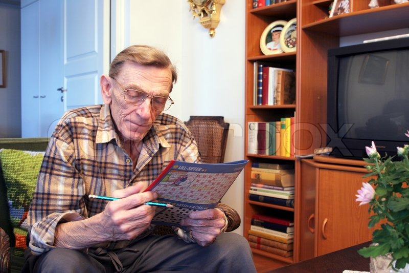 82 years old man solving crossword in his living room, stock photo