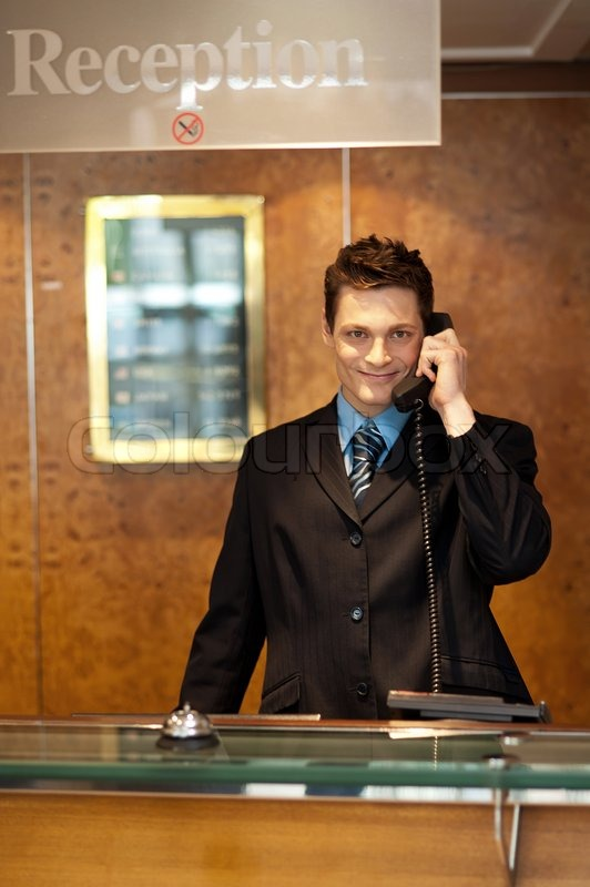 profile shot of a handsome receptionist on the phone