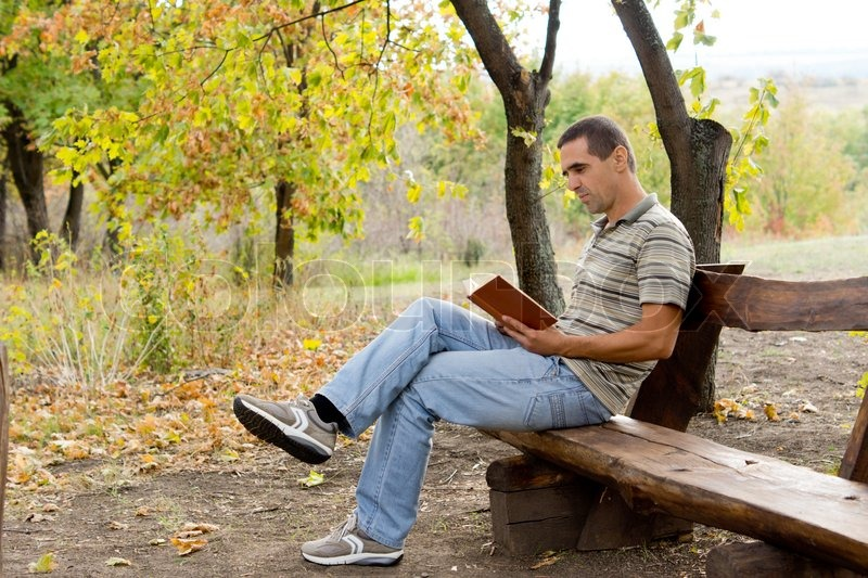 man relaxing reading a book in the country stock photo colourbox