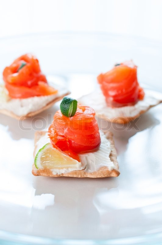 Canapes with salmon cheese lime and rosemary on white for Canape suppliers