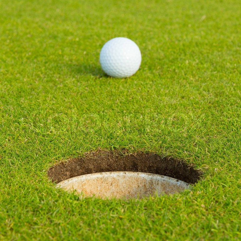 Golf ball in front of the hole, focus on the hole, stock photo