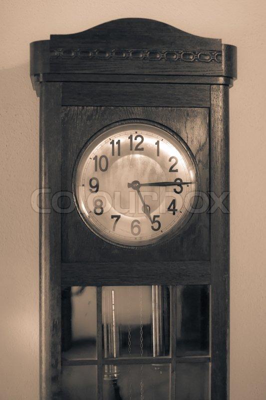 Antique clock in sepia color, stock photo