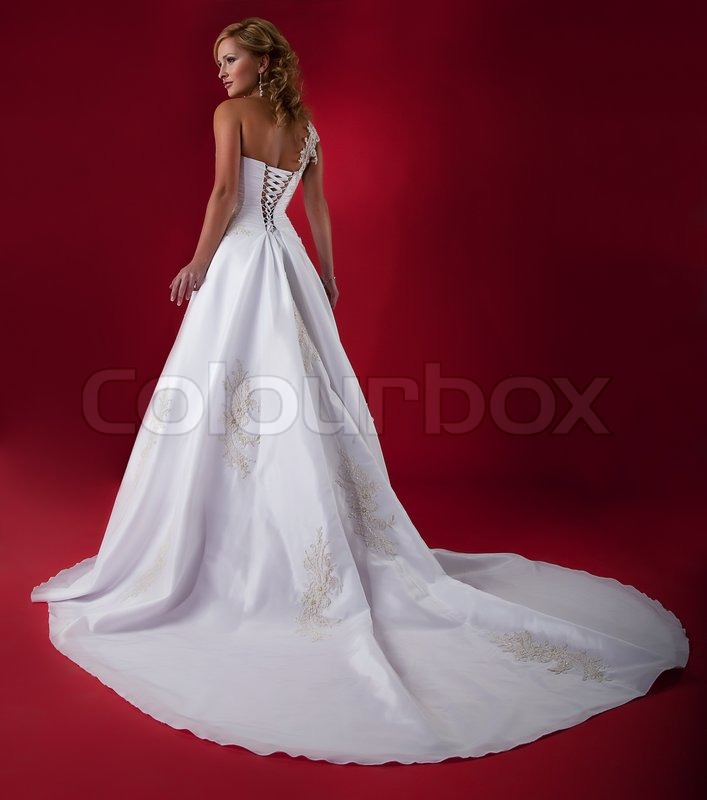 Bride Fashion Model In Long White Bridal Dress On Red Background