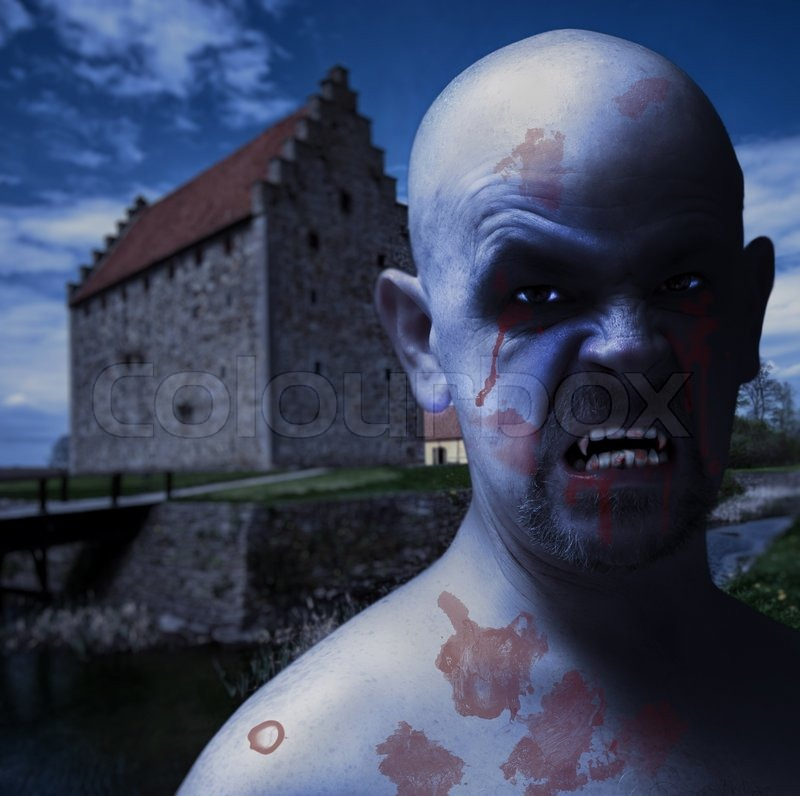 An evil looking vampire male with a spooky castle backdrop ...