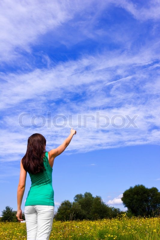 Stock image of 'Young woman pointing the finger into the sky'