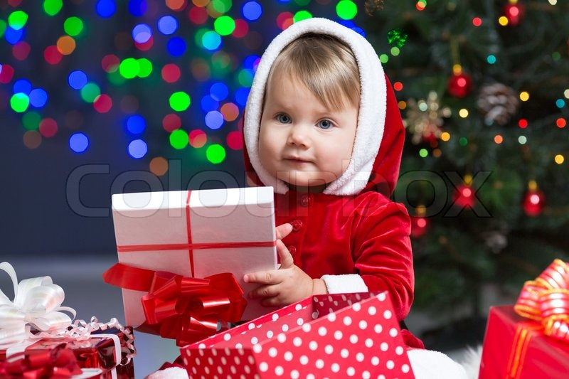 kid girl dressed as santa claus near christmas tree with gifts stock photo - Santa Claus With Kids