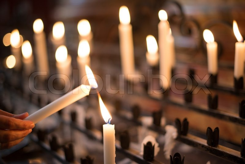 Woman lighting prayer candle aka offering, sacrificial or memorial candles lit in a church, stock photo