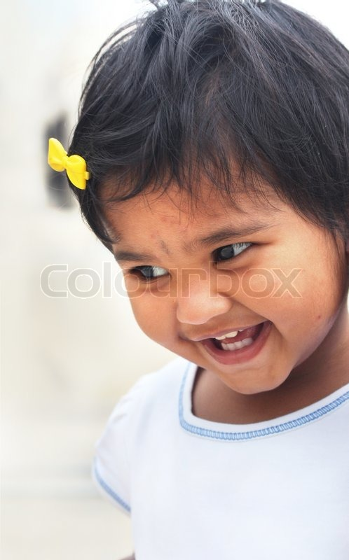 Stock image of 'Photo of beautiful and blissful indian baby girl with expressive eyes and photogenic face expressing toddler's innocence with a pretty smile The child is of pre school age and is of indian origin'