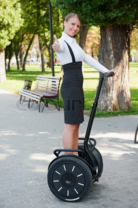 Woman Riding On Segway And Showing Thumbs Up Stock Photo