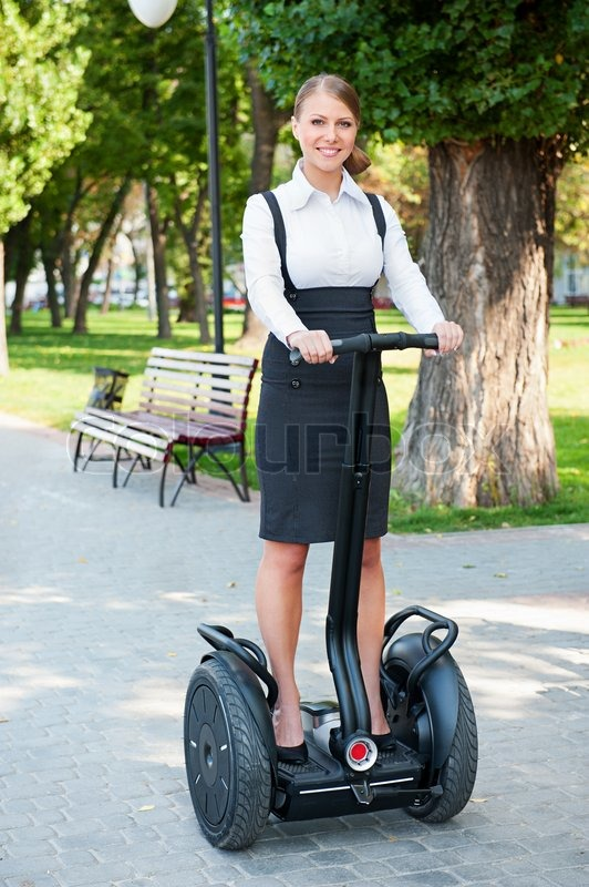 Businesswoman Riding On The Segway In Park Stock Photo
