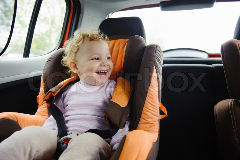 Happy child smiling in car seat, stock photo
