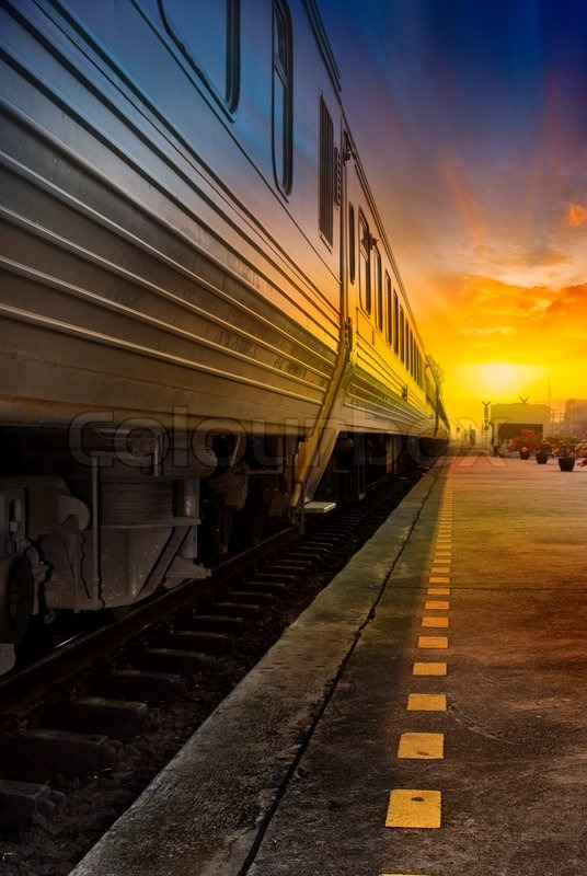 Train passing by in orange sunset | Stock Photo | Colourbox