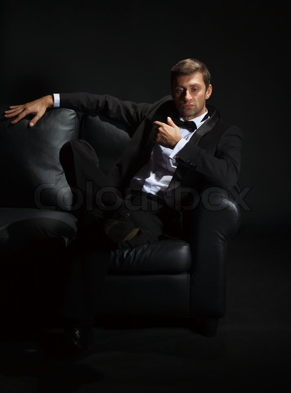 Handsome man in a tuxedo on couch | Stock Photo | Colourbox