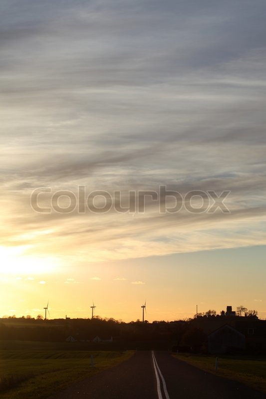 Danish evening landscape with windturbines and country church in silhouette, stock photo