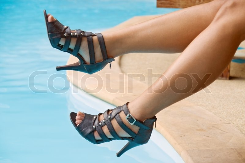 Female legs over blue water, stock photo