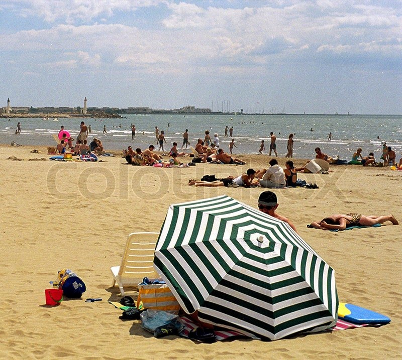 Large Group Of People Relaxing On Beach